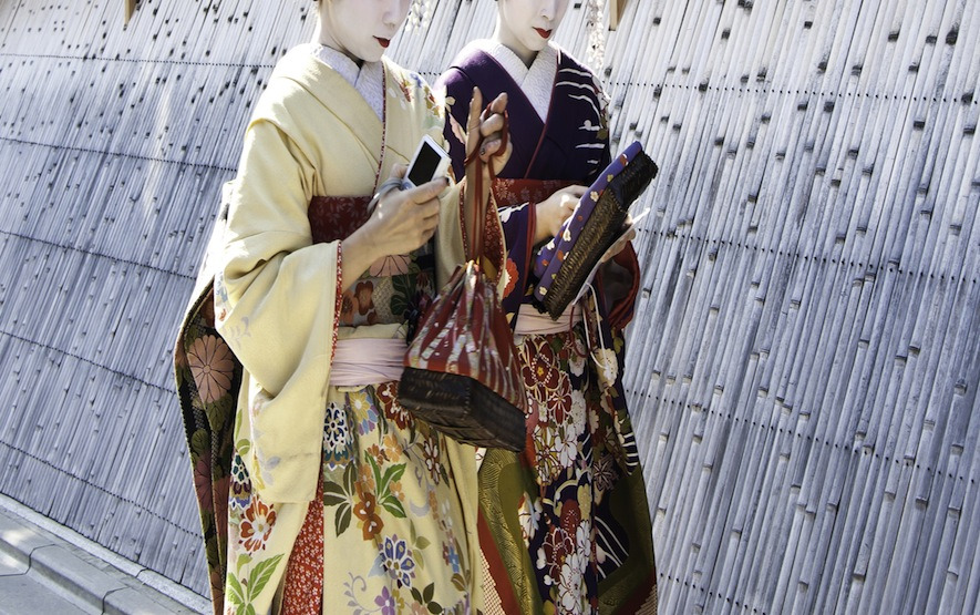Geishas walking by an old street
