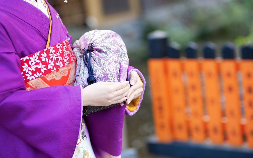 Maiko's hands holding the traditional bag